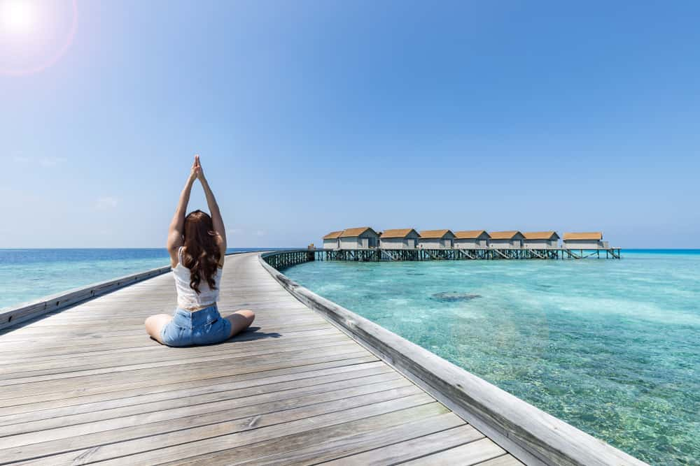 young woman doing yoga in the Maldives